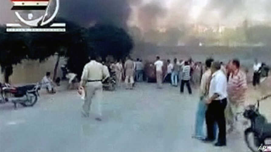 People gather in a street in Hama as smoke rises in the background in this video image posted on a social media website on August 2, 2011 (the authenticity of the video from which this image was taken cannot be independently verified)