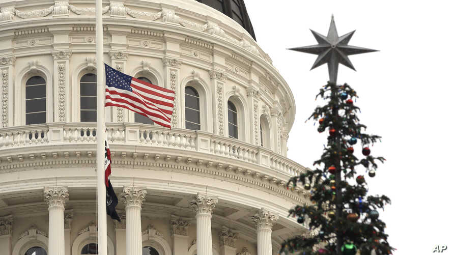 Flags fly at half staff at the Capitol, in Sacramento, Calif., to honor the victims of a mass shooting in San Bernardino, California, Dec. 2, 2015.