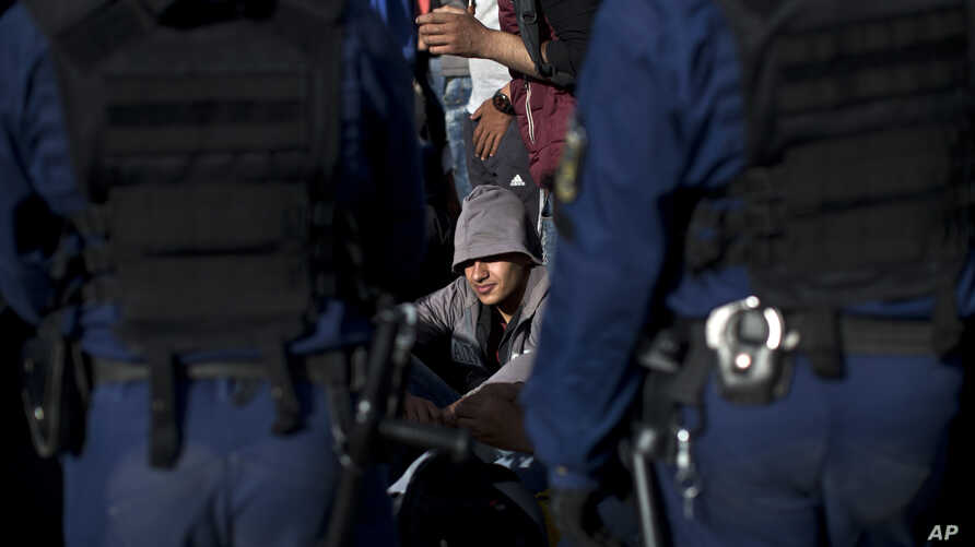 FILE - A man sits on the side of a road as he and a group of migrants and refugees are surrounded by Hungarian police officers in Roszke, Hungary, Sept. 7, 2015.
