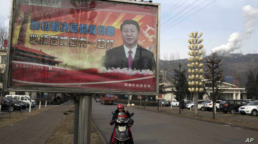 """FILE - A billboard shows Chinese President Xi Jinping with the slogan """"To exactly solve the problem of corruption, we must hit both flies and tigers,"""" in Gujiao, in northern China's Shanxi province, Feb. 6, 2015."""