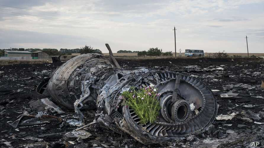 Flowers are placed on a plane engine at the crash site of a Malaysia Airlines jet near the village of Hrabove, eastern Ukraine, July 19, 2014.
