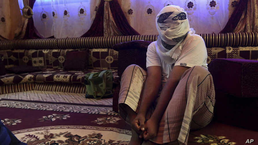 A former detainee shows how he was kept in handcuffs and leg shackles while held in a secret prison at Riyan airport in the Yemeni city of Mukalla, May 11, 2017.
