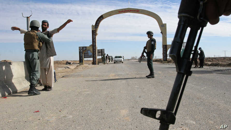 FILE - In this Feb. 26, 2015 file photo, Afghan security police stand guard at checkpoint in Helmand province, south of Kabul, Afghanistan. The Obama administration is abandoning plans to cut the number of U.S. forces in Afghanistan to 5,500 by year'