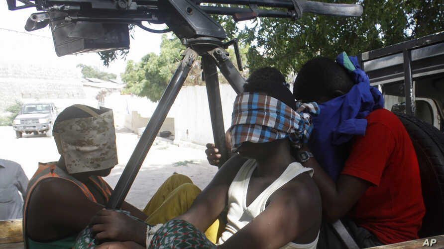 FILE - Suspected Al-Shabab militants captured during an attack on an African Union base are seen in Mogadishu, Somalia, Dec. 25, 2014.