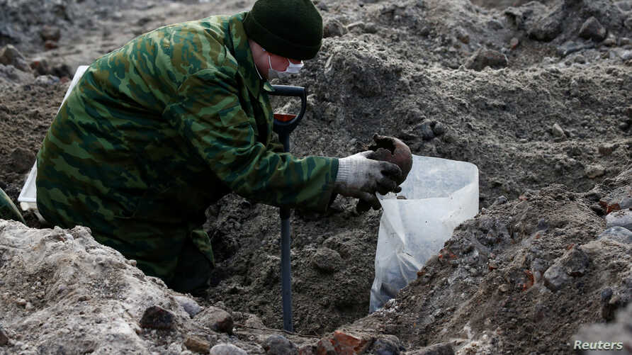 "A soldier from a special ""search battalion"" of Belarus Defence Ministry takes part in the exhumation of a mass grave containing the remains of about 730 prisoners of a former Jewish ghetto, discovered at a construction site in the centre of Brest, Be"