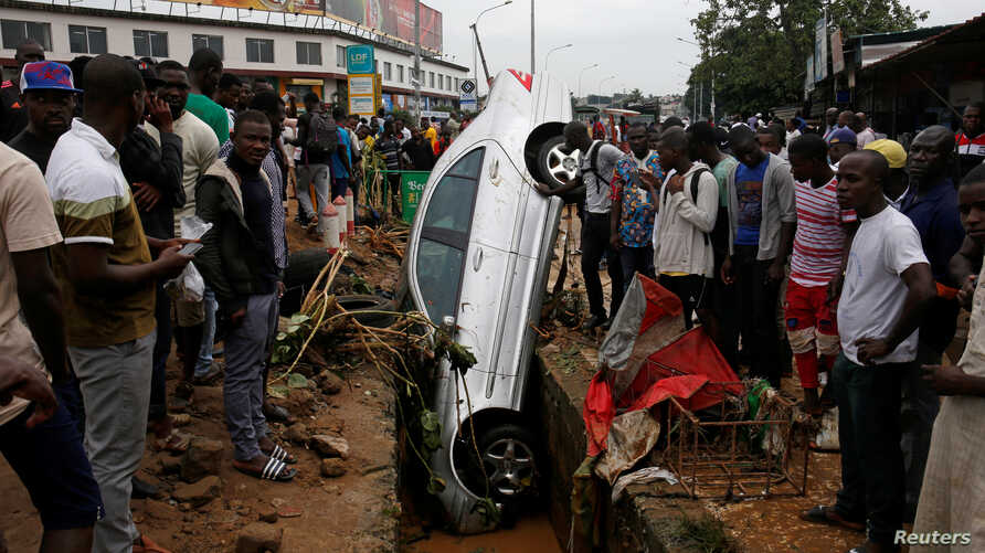 People look at a car in a sewer after a flood in Abidjan, Ivory Coast, June 19, 2018.