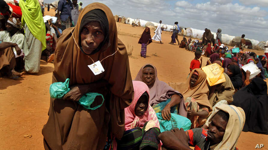 FILE -  Somali refugees walk through an area housing new arrivals, on the outskirts of Hagadera Camp outside Dadaab, Kenya.