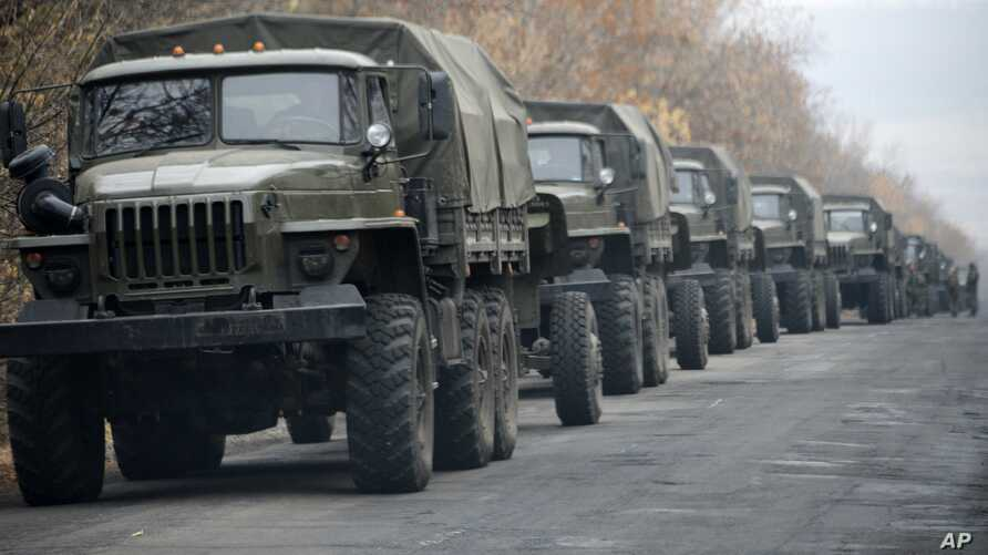 Unmarked military vehicles are parked on a road outside the separatist rebel-held eastern Ukrainian town of Snizhne, 80 kilometers from Donetsk, Nov. 8, 2014.