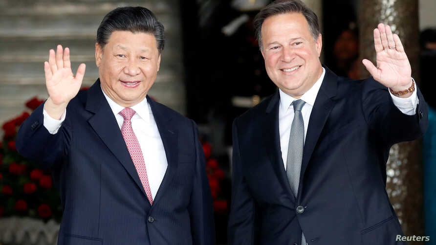 China's President Xi Jinping and his Panamanian counterpart Juan Carlos Varela wave to journalists before a private meeting as part of Xi's first state visit to Panama, at Presidential Palace in Panama City, Panama, Dec. 3, 2018.