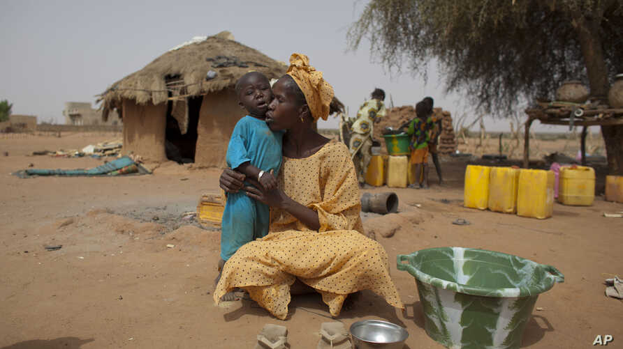 Maryam Sy comforts her 2-year-old son Aliou Seyni Diallo, the youngest of nine, after a neighbor gave him dry couscous to stop him from crying with hunger, May 1, 2012.