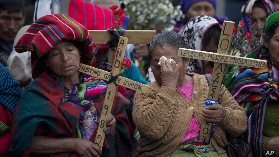Indigenous women pray holding wooden crosses during a ceremony by human rights activists in front of the Supreme Court in Guatemala City, Feb. 25, 2016.