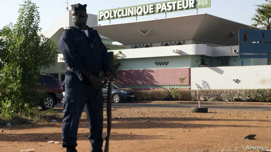 A police officer stands guard outside the quarantined Pasteur Clinic in Bamako, Nov. 12, 2014. The government of Mali confirmed the country's second case of Ebola late on Tuesday and police were deployed outside the clinic in the capital, Bamako, tha...
