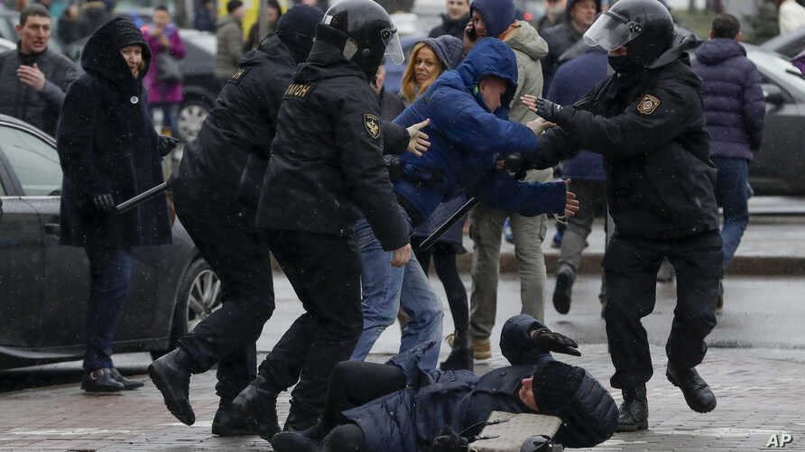 A woman, pushed to the ground by Belarus police, tries to defend herself during an opposition rally in Minsk, March 25, 2017. A cordon of club-wielding police blocked the demonstrators' movement along Minsk's main avenue near the Academy of Science. ...