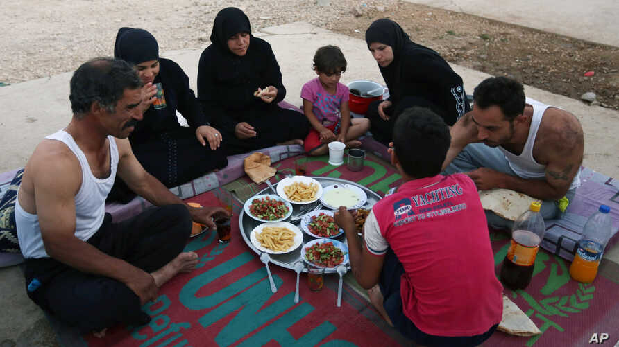 Syrian refugee family members break their fasting outside their tent at a refugee camp in the eastern town of Marj in Bekaa valley, Lebanon, June 29, 2014.