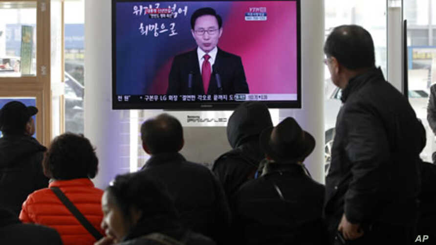 People watch a TV screen reporting South Korean President Lee Myung-bak delivers New Year's speech to the nation, at the Seoul Train Station in Seoul, South Korea, January 2, 2012.