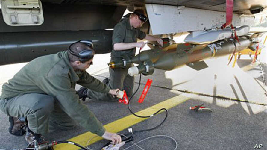 French military ground crew prepare a Mirage 2000 jet fighter for a mission to Libya, at Solenzara 126 Air Base, Corsica, Mar 23 2011