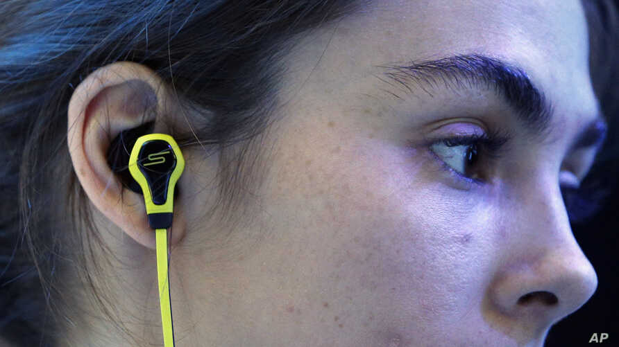 A model wears SMS Audio BioSport In-Ear Headphones at the Intel booth during the International CES, in Las Vegas, Jan. 6, 2015.