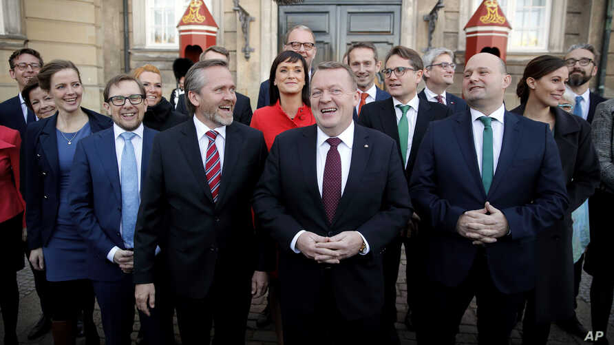 Danish Prime Minister Lars Loekke Rasmussen, center, presents his new government with 22 ministers in front of the Amalienborg Palace in Copenhagen, Monday, Nov. 28, 2016. At left is Foreign Minister Anders Samuelsen.