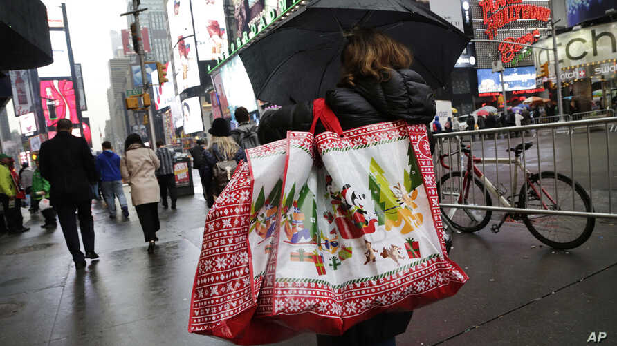 FILE - A woman walks through Times Square with holiday shopping bags, in New York, Dec. 2, 2015.