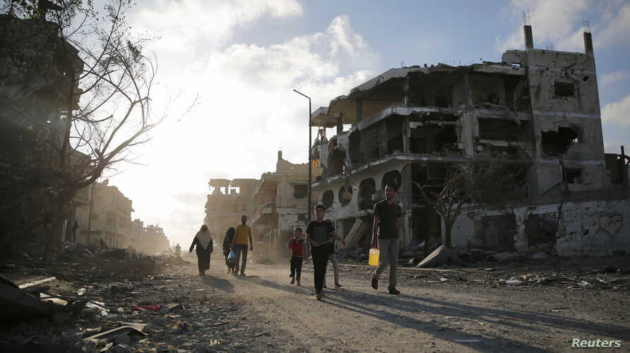 Palestinians walk amid the ruins of destroyed homes in the Shejaia neighbourhood, which witnesses said was heavily hit by Israeli shelling and air strikes during an Israeli offensive, in Gaza City, August 6, 2014.