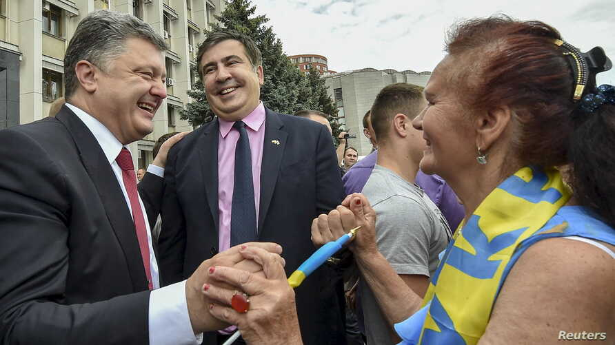 Ukrainian President Petro Poroshenko (L) and governor of Odessa region Mikheil Saakashvili (C) are greeted by a local resident near the regional state administration in Odessa, May 30, 2015.