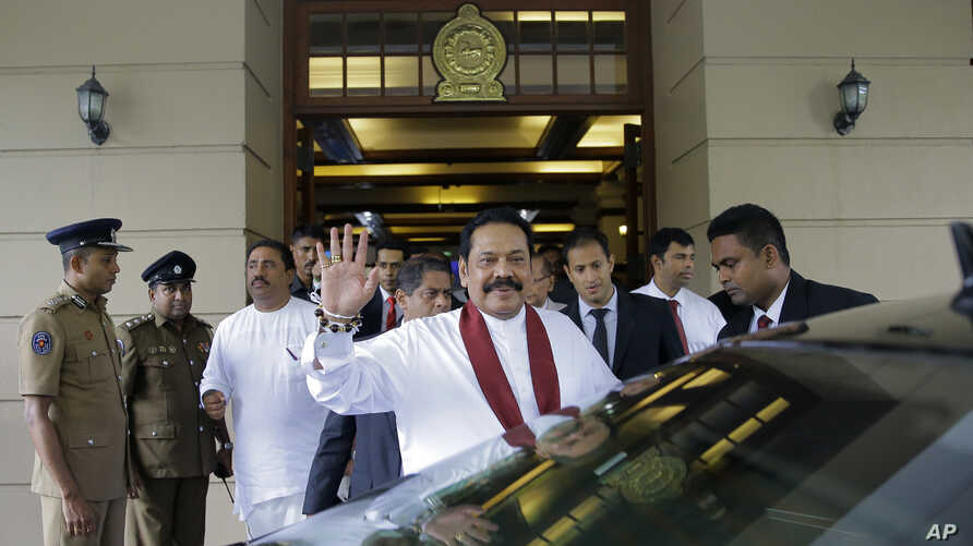 Sri Lankan Prime Minister Mahinda Rajapaksa waves after assuming duties as finance minister in Colombo, Sri Lanka, Oct. 31, 2018.