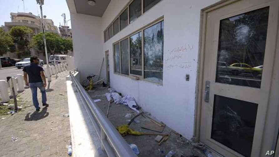 A man checks the damaged U.S. embassy after pro-government protesters attacked the embassy compound in Damascus, Syria, July 11, 2011