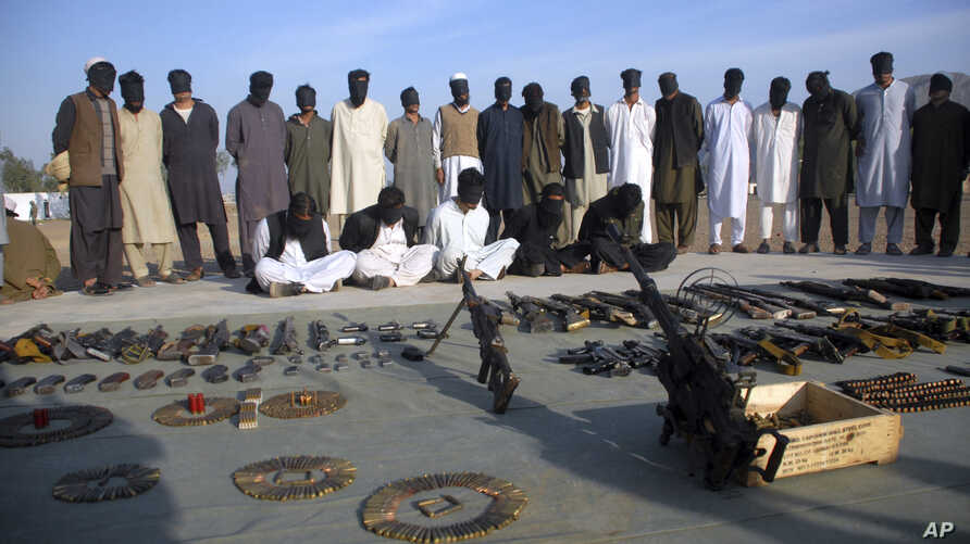 Arrested suspects and recovered weapons display for media by Pakistan paramilitary forces following a search operation in Shah Kass, an area of Pakistani Khyber tribal region along Afghan border, March 3, 2017.