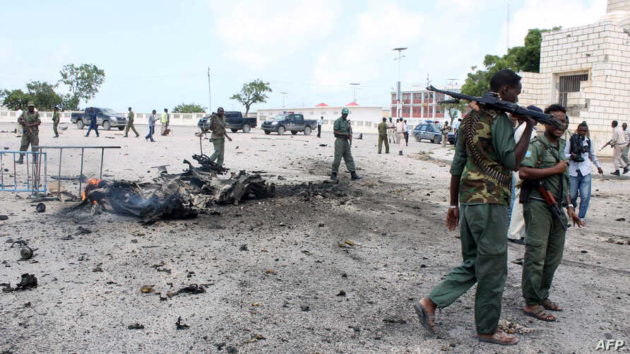 Somalian security forces walk past the remains of a car on July 5, 2014  after it exploded outside the Somali parliament building in Mogadishu.