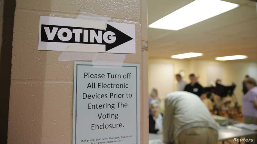 Sign points way to voting booths during presidential primary election at Sharon Presbyterian Church, Charlotte, North Carolina, March 15, 2016.