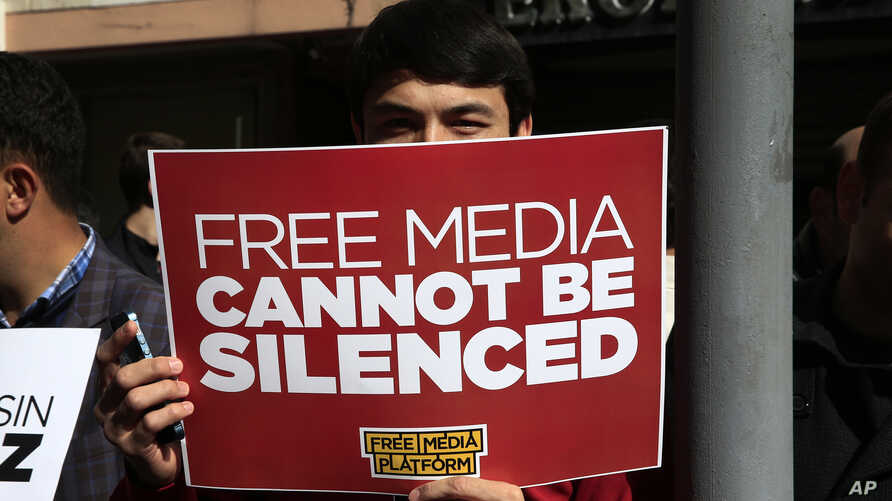 FILE - A protester is seen holding a placard at a rally in support of press freedom near the headquarters of a media company in Istanbul, Wednesday, Oct. 28, 2015.