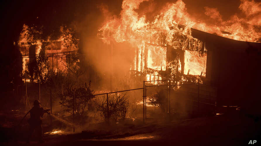 A firefighter sprays water as flames from a wildfire consume a residence near Oroville, Calif., on Sunday, July 9, 2017. Evening winds drove the fire through several neighborhoods leveling homes in its path.
