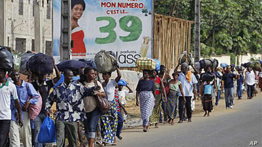 Residents of the Abobo district carry their belongings as they flee the neighborhood which has become a hub for street violence in the nation's ongoing political standoff, in Abidjan, Ivory Coast, February 28, 2011