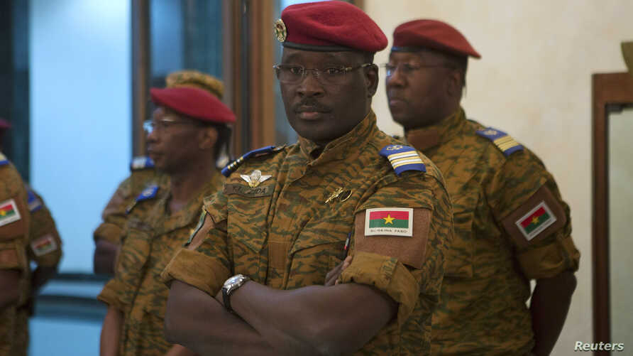Burkina Faso Prime Minister Yacouba Isaac Zida listens as an official reads the names of transitional government ministers in Ouagadougou Nov. 23, 2014.