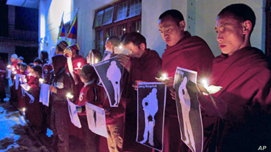 January 25, 2012, file photo shows Tibetan Buddhist monks holding pictures of Tibetans they claim were allegedly shot by Chinese security forces earlier this week, during a candlelight vigil in Dharamsala, India
