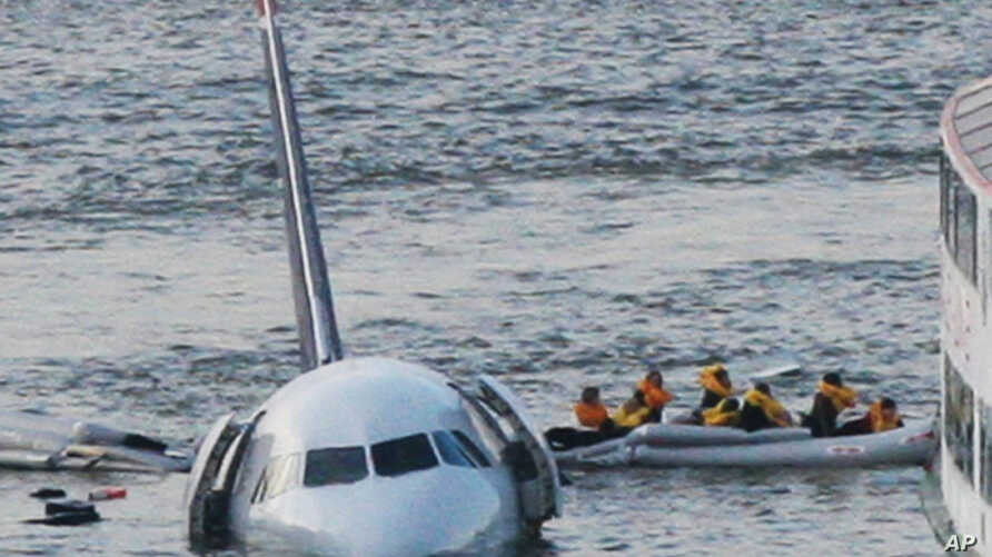 Sully Movie Investigators: FILE - In this Jan. 15, 2009 file photo, passengers in an inflatable raft move away from an Airbus 320 US Airways aircraft that has gone down in the Hudson River in New York. Accident investigators say they object to their