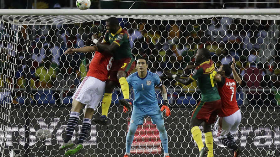 Egypt goalkeeper Essam El Hadary, center, watches as Cameroon's Nicolas Nkoulou, 2nd left, jumps to score his side's first goal during the African Cup of Nations final soccer match between Egypt and Cameroon at the Stade de l'Amitie, in Libreville, G