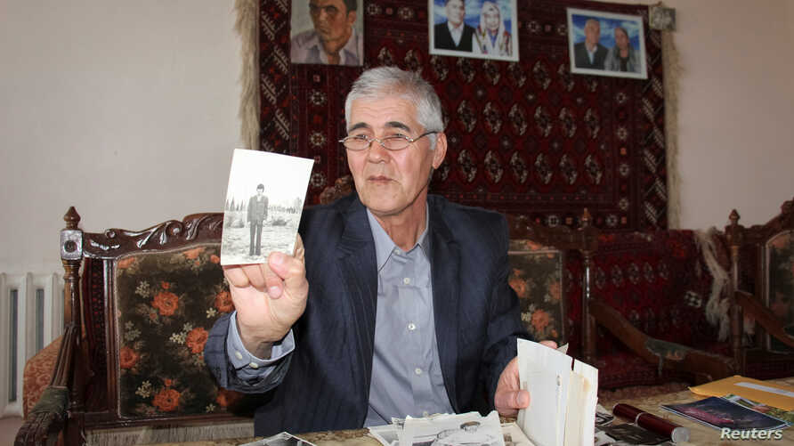 Muhammad Bekjanov, 63, a newspaper editor who was jailed for 18 years, shows a photo of himself taken at a younger age, after being released in February at his home in Yangibazar, Uzbekistan, March 1, 2017.