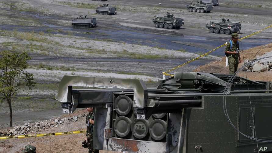 "A U.S.-made HIMARS (High Mobility Advanced Rocket System) is displayed amidst armored personnel carriers after taking part in the 11-day joint U.S.-Philippines military exercise dubbed ""Balikatan 2016,""  April 14, 2016 at Crow Valley, north of Manila"