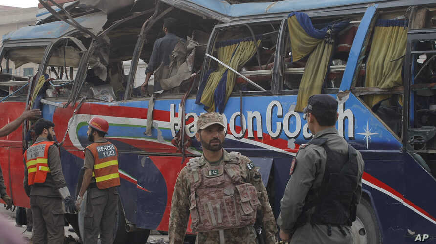 Pakistani security personnel examine a bus following a bomb blast in Peshawar, Pakistan, Wednesday, March 16, 2016.