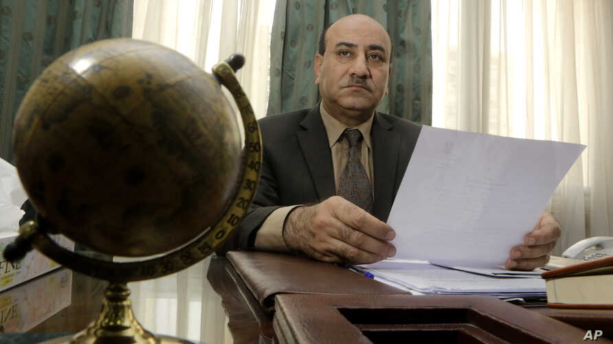 FILE - Hesham Genena, the head of Egypt's oversight body, holds documents at his office in Cairo, April 16, 2014.
