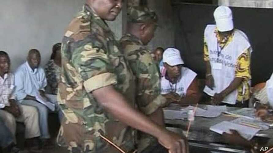 A member of Guinea's military casts a ballot during Guinea's first round of presidential elections