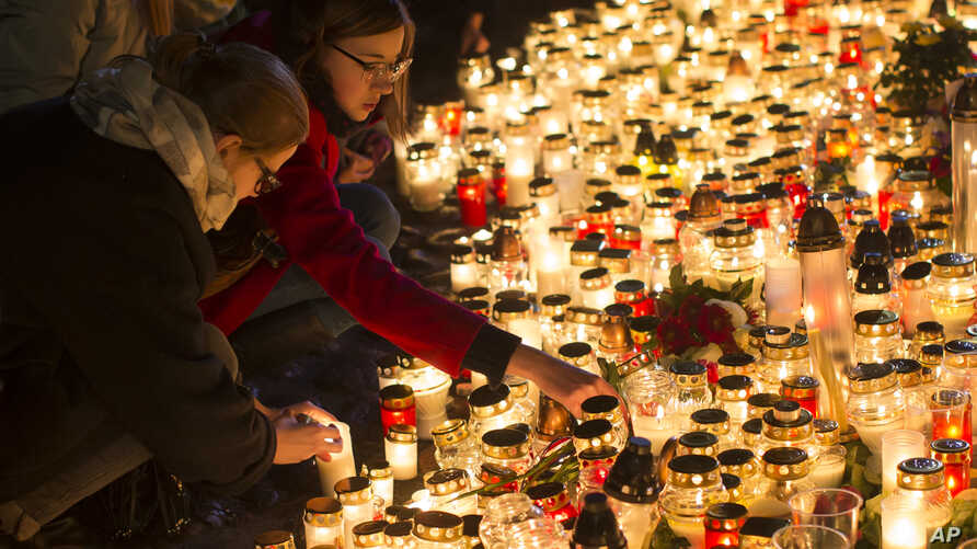 Candles are placed outside the French embassy in Vilnius, Lithuania, for the victims in Friday's attacks in Paris, Nov. 14, 2015.