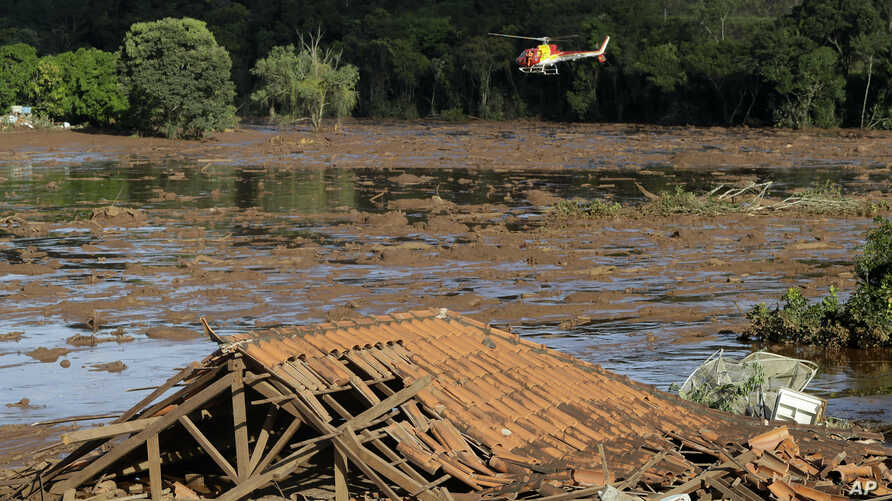 Rescue workers in a helicopter search a flooded area after a dam collapsed in Brumadinho, Brazil, Sunday, Jan. 27, 2019.