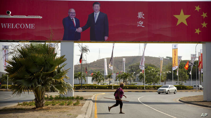 In this Nov. 15, 2018, photo, a woman crosses the street near a billboard commemorating the state visit of Chinese President Xi Jinping in Port Moresby, Papua New Guinea.