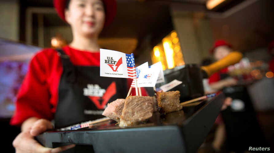 FILE - A hostess holds a tray of sliced American beef at an event to celebrate the re-introduction of American beef imports to China, in Beijing, China.