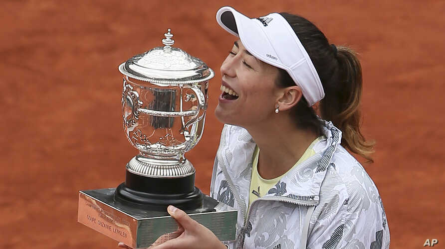 Spain's Garbine Muguruza holds the trophy after winning the final of the French Open tennis tournament against Serena Williams of the U.S. in two sets 7-5, 6-4, at the Roland Garros stadium in Paris, France, June 4, 2016.
