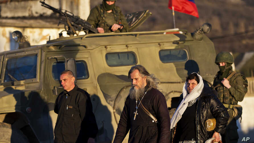 Archbishop Clement of Ukrainian Orthodox church (center) walks past a pro-Russian armored vehicle and soldiers outside an Ukrainian military base in Perevalne, Ukraine, March 15, 2014.