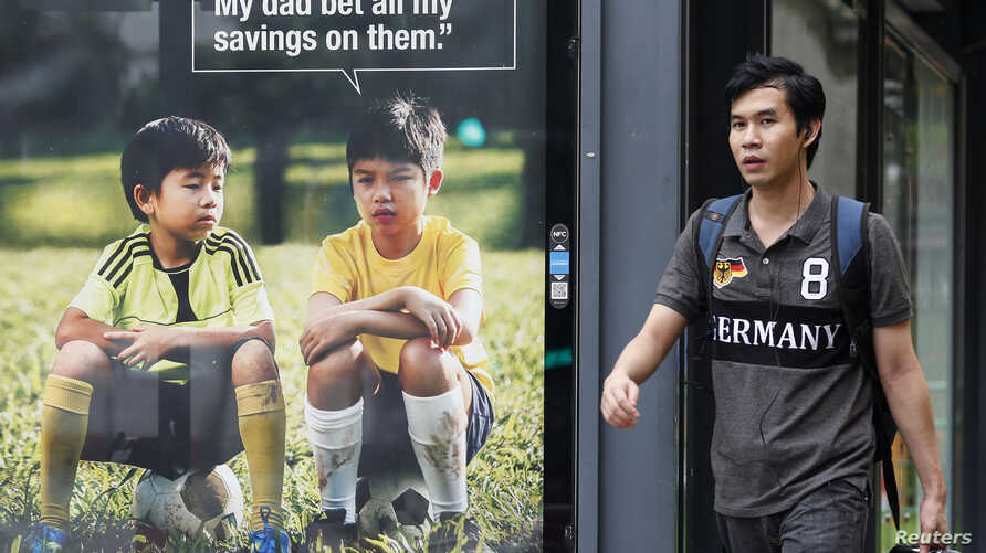 A man walks past a World Cup anti-gambling advertisement at a taxi stand in Singapore, July 9, 2014.