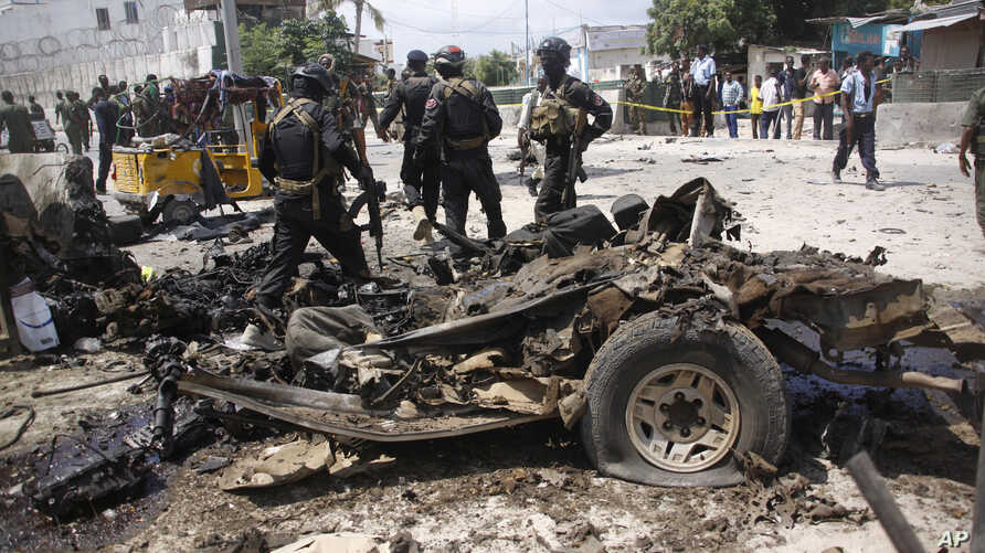Somali soldiers stand near the wreckage of a car used in a suicide car bomb attack outside the Criminal Investigation Department (CID) in Mogadishu, Somalia, July 31, 2016.